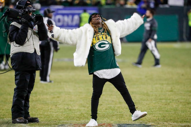 Rapper Lil Wayne sings during a break during the second half of an NFL divisional playoff football game between the Green Bay Packers and the Seattle Seahawks Sunday, Jan. 12, 2020, in Green Bay, Wis.
