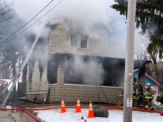 Firefighters battle thick smoke as a blaze continued out of control shortly before noon Friday, Jan. 17, in the 700 block of North Hartwell Avenue in Waukesha. Two dogs were killed in the fire.