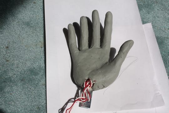 Clay is shown wrapped around the wire and wood to make a hand.