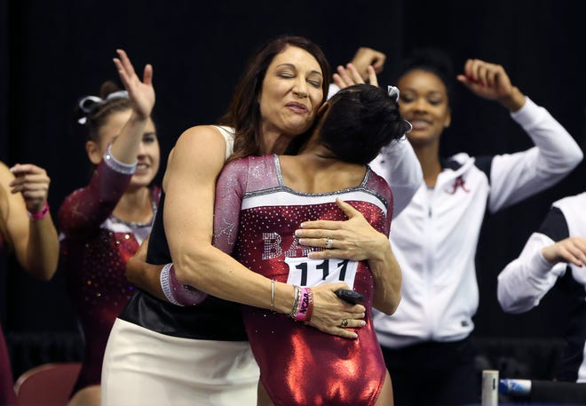 Apr 16, 2016; Fort Worth, TX, USA;  Alabama Crimson Tide gymnast Aja Sims (111) hugs head coach Dana Duckworth after her balance beam routine during the team finals of the 2016 NCAA Women's Gymnastics Championships at Fort Worth Convention Center Arena. Mandatory Credit: Kevin Jairaj-USA TODAY Sports
