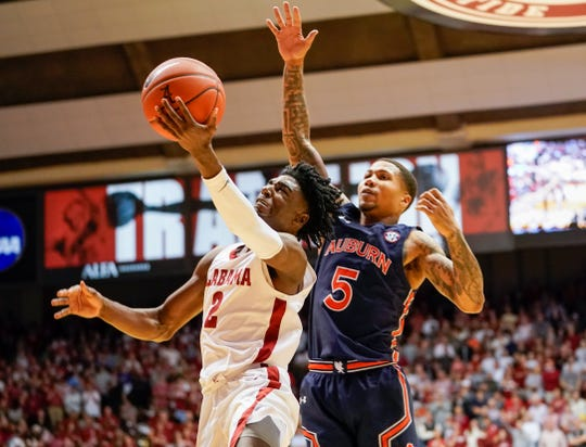 Jan 15, 2020; Tuscaloosa, Alabama, USA; Alabama Crimson Tide forward Herbert Jones (1) drives to the basket against Auburn Tigers guard J'Von McCormick (5) at Coleman Coliseum. Mandatory Credit: Marvin Gentry-USA TODAY Sports