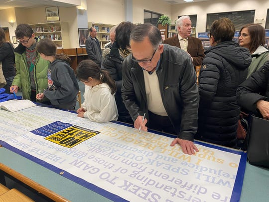 People sign a No Place for Hate banner at Glen Rock High School as part of an Anti-Defamation League school project Jan. 15, 2020.