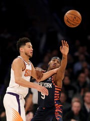Devin Booker #1 of the Phoenix Suns and RJ Barrett #9 of the New York Knicks fight for the ball in the first half at Madison Square Garden on January 16, 2020 in New York City.
