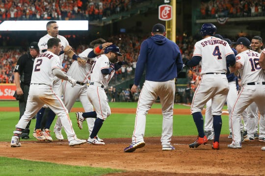 Jose Altuve #27 of the Houston Astros comes home to score after his walk-off two-run home run to win Game 6 of the American League Championship Series 6-4 against the New York Yankees at Minute Maid Park on October 19, 2019 in Houston, Texas.