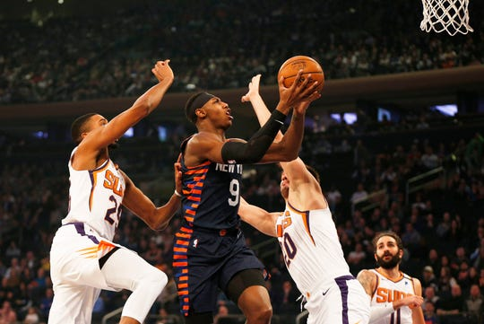 Jan 16, 2020; New York, New York, USA; New York Knicks guard RJ Barrett (9) goes up for a shot between Phoenix Suns forward Mikal Bridges (25) and Phoenix Suns forward Dario Saric (20) during the first half at Madison Square Garden.