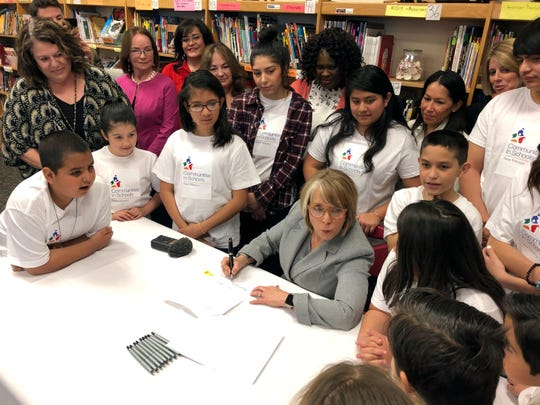In this April 3, 2019 file photo, New Mexico Gov. Michelle Lujan Grisham signs legislation to raise teacher salaries and increase annual spending on public schools by almost a half-billion dollars at Salazar Elementary School in Santa Fe. New Mexico Democrats pushed forward a progressive agenda as the booming oil industry made headlines in 2019 with record revenues for the state's coffers.