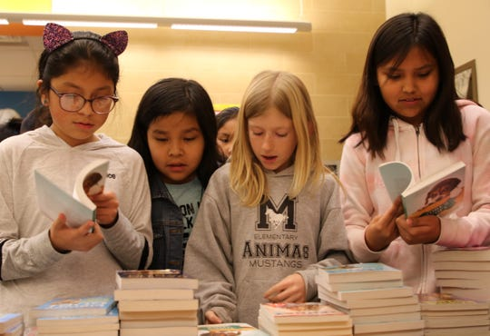 From left foreground, fourth grade students Chelsea Gonzalez Garcia, Hailey Collier and Keyaira Chee browse a selection of books on Jan. 17, 2020 at Animas Elementary School in Farmington.