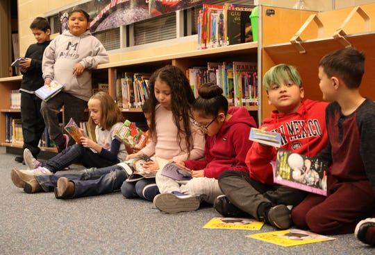 Animas Elementary School students check out the books they picked from a book giveaway organized by the Rio Del Sol Kiwanis Club on Jan. 17 in Farmington.