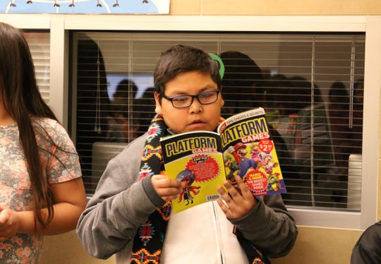 Fourth grade student Ezekiel Martin reads his book during the book giveaway on Jan. 17 at Animas Elementary School in Farmington.
