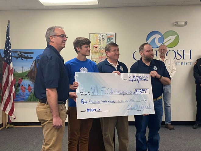 Oshkosh West High School junior John Weigand presents a check worth $5,354 to the Wisconsin Law Enforcement Association President Tony Nardi and members Kevin Konrad and Jeremy Scott on Friday, Jan. 17, 2020, at the Oshkosh Area School District Administration Office.