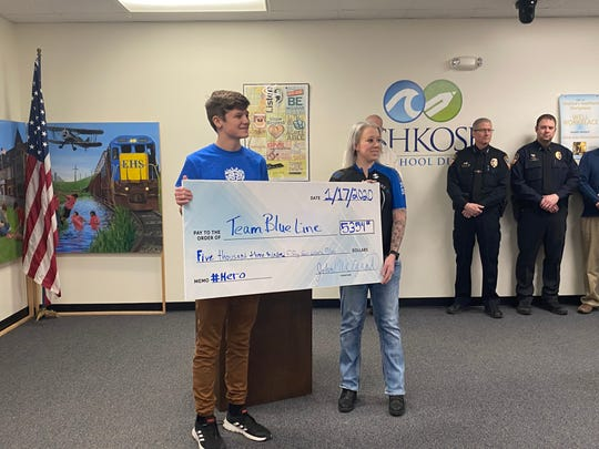 Oshkosh West High School junior John Weigand presents a check of $5,354 to Kimberly Kuehl Zoch of the police charity Thin Blue Line on Friday, Jan. 17, 2020, at the Oshkosh Area School District Administration Office.
