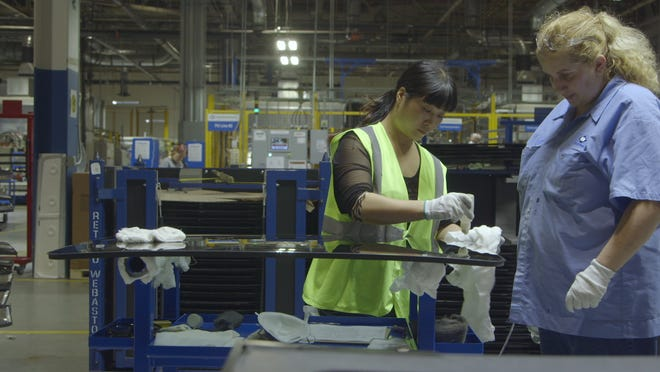 """A Chinese worker and an American worker in a scene from """"American Factory."""""""