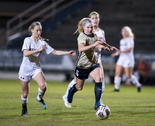 Delaney Williams (5) dribbles the ball during the Navarre vs Gulf Breeze girls soccer game at Gulf Breeze High School on Thursday, Jan. 16, 2020.