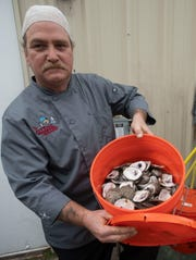 Frank Nelson, an employee at The Cutting Board in Milton, shows a bucket of discarded oysters shell collected by the restaurant on Friday.