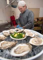 Frank Nelson, an employee at The Cutting Board in Milton, shucks a platter of raw oysters Friday. The restaurant is one of three in Santa Rosa County that are participating in a new oyster shell recycling pilot program. The Cutting Board goes through about 2,000 pounds of oysters in a week.