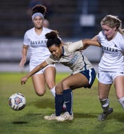 Mya Swinton (11) maintains control of the ball while fending off Autumn Slaybaugh (15) during the Navarre vs Gulf Breeze girls soccer game at Gulf Breeze High School on Thursday, Jan. 16, 2020.