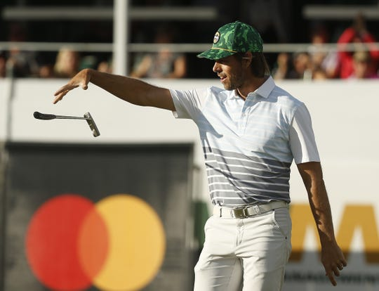 """Aaron Baddeley celebrates with a """"club drop"""" after making a birdie putt on the 16th hole during first round of the Waste Management Phoenix Open at TPC Scottsdale in Scottsdale, Ariz. on January 31, 2019."""