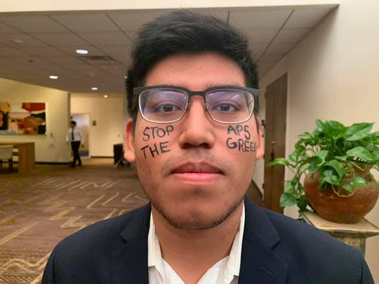 "Brian Mecinas of AZ Youth Climate Strike had the phrase ""Stop the APS Greed"" painted on his face."