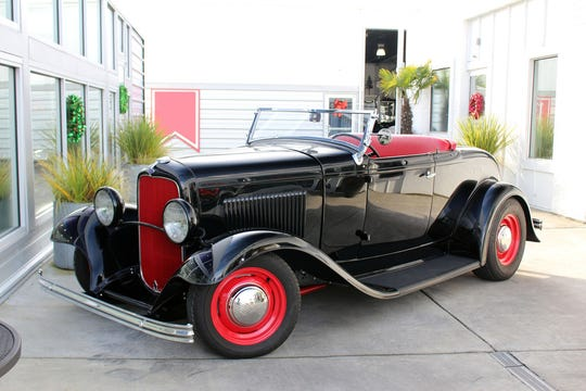 The 1932 Ford Custom Roadster has a classic black finish with red interior, Stewart Warner winged gauges and Mercedes dark gray square-weave carpet.