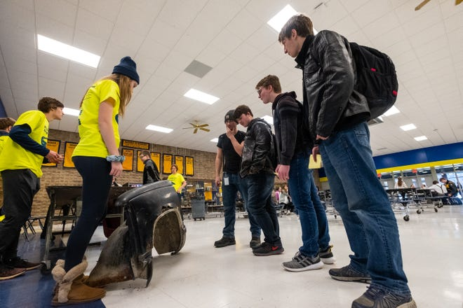 A group of Port Huron Northern students look at a part from a scrapped car at a booth hosted by the school's Strive for a Safer Drive club Friday, Jan. 17, 2020, during the school's lunch period. This is the first year the school has had the student-run program, which aims to help other students develop safer driving habits.