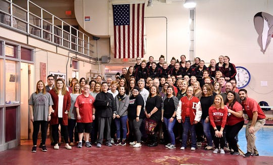 Dover swimming alumni pose with the current team at the diving board of the 45 year old natatorium, Thursday, January 16, 2020. Dover will have a new natatorium in the new high school next season.