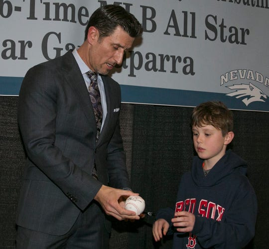 Nomar Garciaparra signs a ball for 9-year-old Brady Costanza during the 36th Annual Bobby Dolan Baseball Dinner in the Reno Ballroom on Thursday, January 16, 2020.
