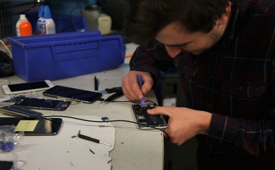 Ben Hayes, Sunnking's mobile electronics repair technician, uses a plastic tool to pull the adhesive out from beneath a lithium-ion battery in an iPhone.