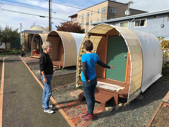 Redding resident Laural Park, left, gets a tour of tiny hut shelter in Eugene, Oregon. Park wants to do the same thing in Shasta County.