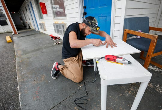 Quinones Martinez Emmanuel Jesus cuts of piece of drop ceiling while making improvements to the Polar Bear Inn in Branson, Mo., on Wednesday, Jan. 15, 2020.