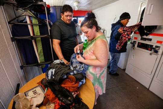 Sarah Andrews, center, and her fiancee Sierra Essman look through a table full of free items in the laundry room of the Travel Inns in Branson, Mo., on Wednesday, Jan. 15, 2020.
