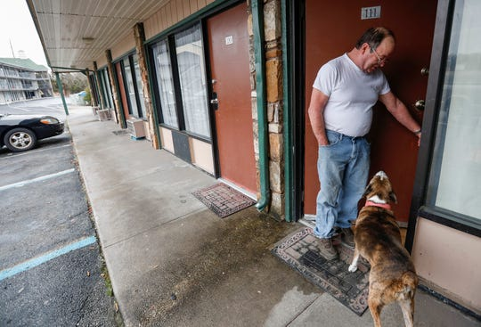 Kevin Smith lets his dog Layla back into his room at the Travel Inns in Branson, Mo., on Wednesday, Jan. 15, 2020.