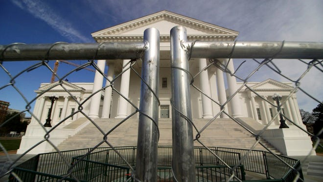The Virginia state Capitol building is surrounded by fencing, Thursday, Jan. 16, 2020 in Richmond, Va., in preparation for Monday's rally by gun rights advocates. Gun-rights groups are asking a judge to block the Virginia governor's ban on firearms at a massive pro-gun rally scheduled for next week. Gov. Ralph Northam on Wednesday, Jan. 15, announced a state of emergency and banned all weapons from the rally at the Capitol.