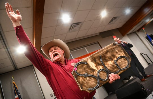 """Ringman Dave Finnila calls out bids while holding a custom-made """"sold"""" sign up for sale during the Minnesota State Auctioneers Association Conference and Show Thursday, Jan. 16, 2020, in St. Cloud."""