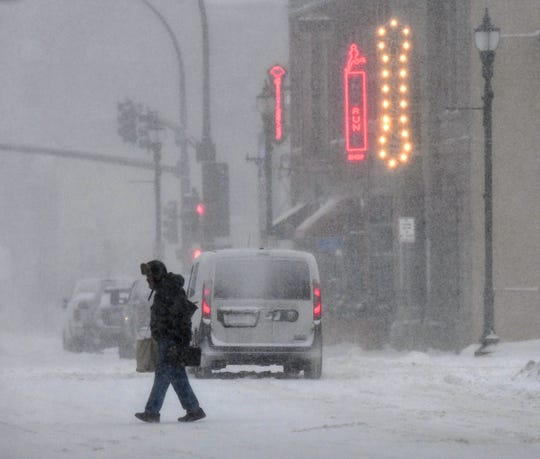 Heavy snow falls as people make their way home after work in downtown St. Cloud Friday, Jan. 17, 2020.