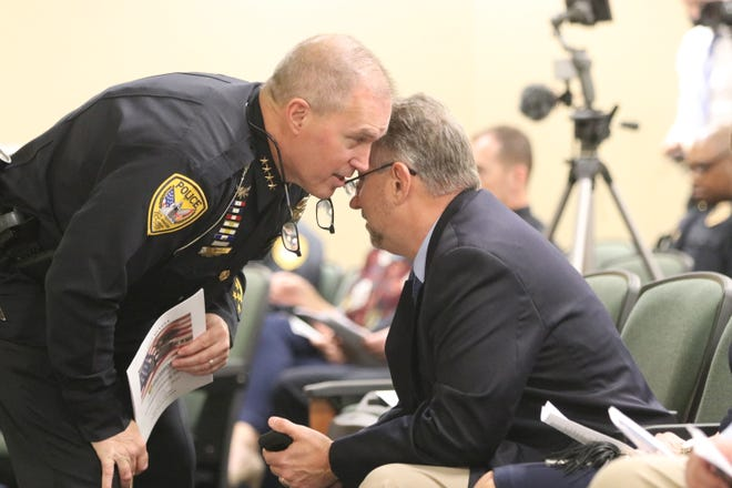Tallahassee Police Chief Lawrence Revell whispers with retiring Interim Chief Steve Outlaw during Friday's ceremony for Outlaw.