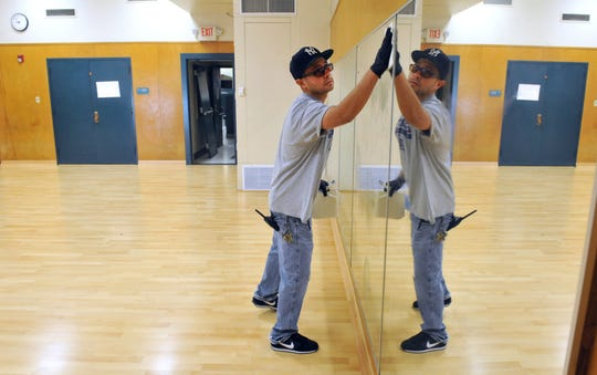 A custodian at Haydock Academy of Arts and Sciences is seen cleaning mirrors in a dance studio when the school was remodeled in 2014. The district is planning to rename the school, getting rid of the Haydock moniker.