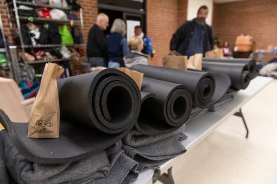 Volunteers line up pads and snacks as the homeless sign in to take shelter from the cold nights at St. Paul's Episcopal Church on Tuesday, January 14, 2020.