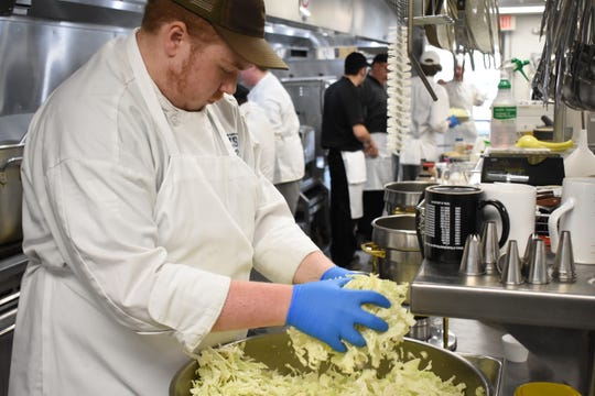 Zane State culinary student Andrew Sceurman prepares food for Friday's Ethnic Food Fair.