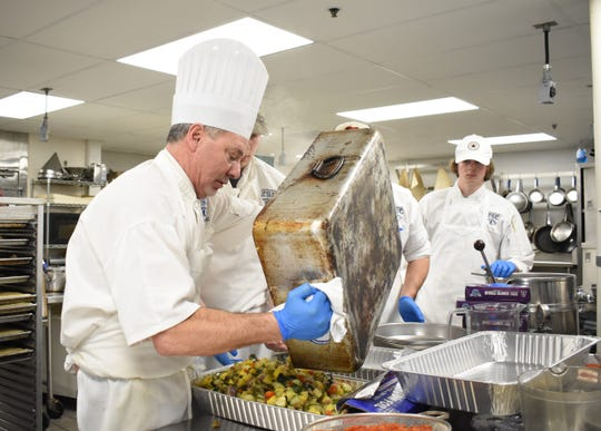 Culinary Program Director Marco Adornetto dumps Ratatouille into trays ahead of Friday's lunch while students Branson Umensetter, Anthony Pridgeon and Nickolas Snyder look on.