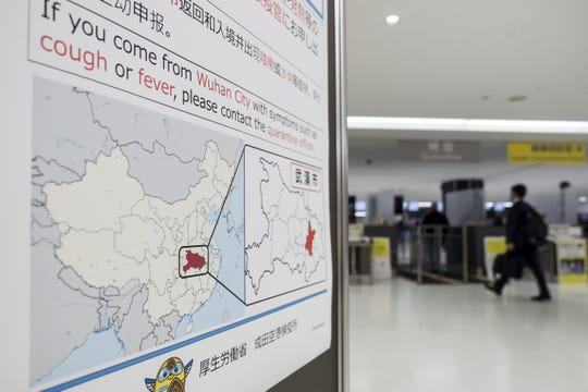 A passenger walks past a notice for travelers from Wuhan, China, displayed near a quarantine station at Narita airport on Jan. 17 in Japan.