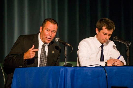 FILE - In this June 23, 2019, file photo, South Bend Police Chief Scott Ruszkowski, left, and Democratic presidential candidate and then-South Bend Mayor Pete Buttigieg answer questions during a town hall community meeting at Washington High School in South Bend, Ind. Buttigieg faced criticism from angry black residents at the emotional town hall meeting, a week after a white police officer fatally shot a black man in the city.