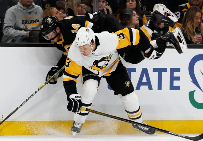 Pittsburgh Penguins defenseman Jack Johnson checks Boston Bruins right wing Chris Wagner during the first period of a game last season. Johnson was placed on waivers Monday and the Penguins plan to buy out the remaining three years of his contract.