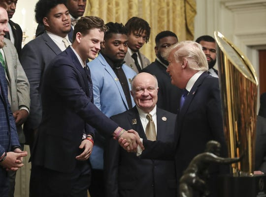 President Donald Trump, right, shakes hands with LSU quarterback Joe Burrow during an event to honor this year's college football national champions in the East Room of the White House on January 17, 2020.