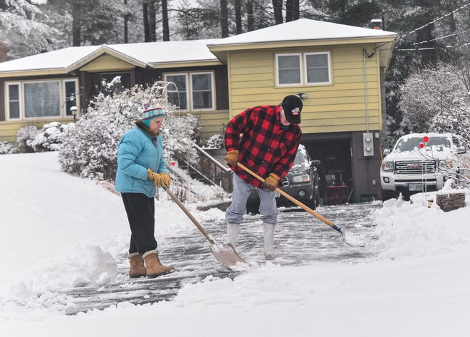 Worley and Sonja Parton of Hinsdale, NH, cross the driveway after a snowstorm on Thursday, January 16, 2020. A snowstorm threw more than half a foot of snow in parts of Maine, New Hampshire and Vermont in Thursday.