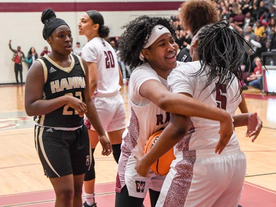 Westside sophomore Destiny Middleton hugs teammate Westside sophomore Keazia Hatten after her last second rebound near T.L. Hanna junior Alexis Glover to end the game 60-59 at Westside in Anderson Friday.