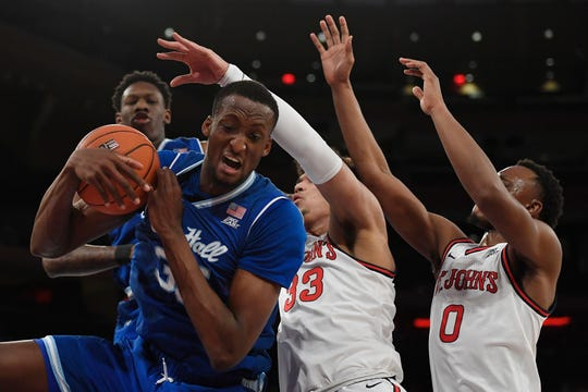 Seton Hall center Romaro Gill (35) catches a rebound against St. John's forward Ian Steere (33) and guard Mustapha Heron (0)