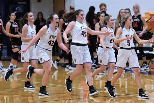 Wylie's Karis Christian (12), Bailey Roberts (42), Ceci Widder (40), Makinlee Bacon (25) and Morgan Travis (5) celebrate their 35-31 win against Aledo at Bulldog Gym on Friday.
