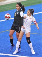 Abilene High's Bertha Sanchez, left, fights Cooper's Megan Melchor for the ball. AHS beat the Lady Cougars 4-0 in the nondistrict game Jan. 17 at Shotwell Stadium.