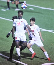 Cooper's Asende Lokendo (18) plays the ball in front of teammate John Michael Albarado and an Abilene High defender. The Eagles beat Cooper 3-1 in the nondistrict game Friday, Jan. 17, 2020, at Shotwell Stadium.