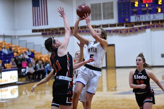 Wylie's Morgan Travis (5) puts up a shot over Aledo's Raylee McDonald (11) on Friday. Travis scored nine points as the Lady Bulldogs won 35-31 for their first District 4-5A win of the year.